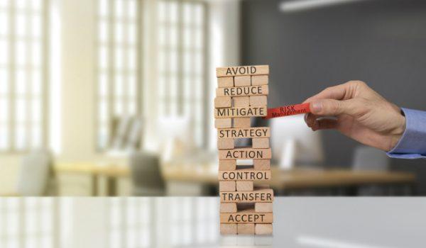 tessere di legno a torre che rischiano di cadere con la tessera rossa del risk management